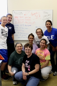 Catholic heart work camp  youth with Amy Brock, Soup of Success production manager, in front of a white board that shows quantities they made.