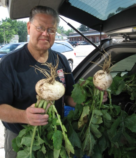 Man holding 2 large freshly pulled turnips